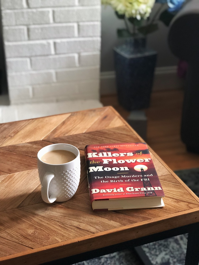 picture of a book on a coffee table with a mug of coffee